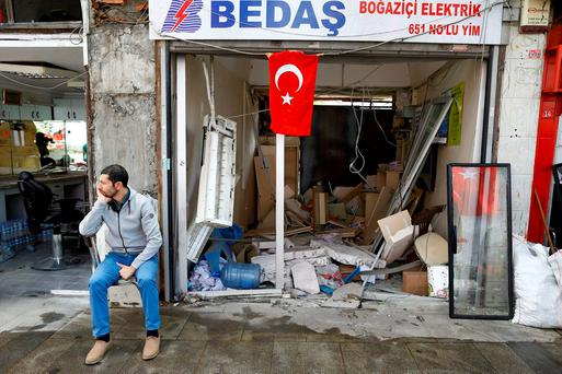 A man sits in front of a damaged shop near the scene of Tuesday's car bomb attack on a police bus, in Istanbul, Turkey, June 8, 2016. REUTERS/Osman Orsal