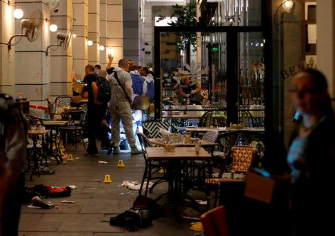 Israeli policemen work inside a restaurant following a shooting that took place in the center of Tel Aviv