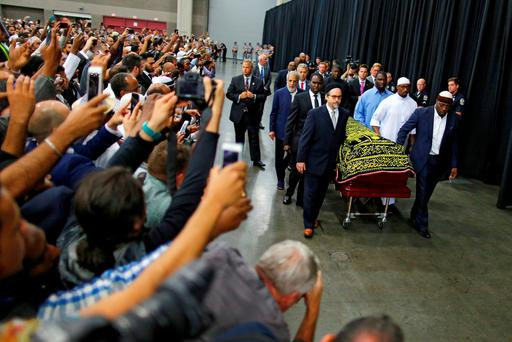 Worshipers and well-wishers take photographs as the casket with the body of the late boxing champion Muhammad Ali is brought for his jenazah, an Islamic funeral prayer, in Louisville, Kentucky. Reuters/Carlos Barria