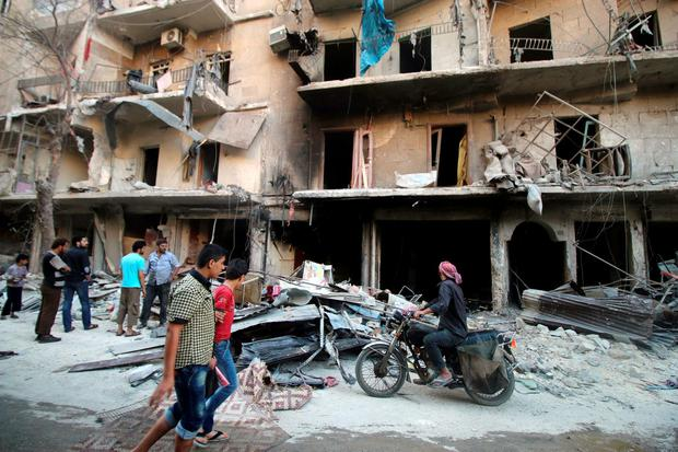 Men inspect damage after an air strike on Aleppo's rebel-held al-Shaar neighbourhood, Syria. Photo: Reuters