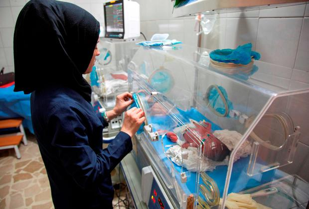 A Syrian nurse stands next to incubators with newborns at a children's hospital in Aleppo. Photo: Getty