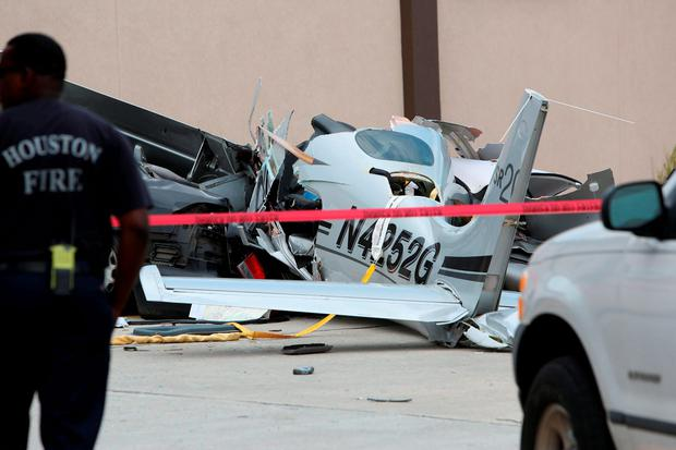 Authorities investigate the scene where a small plane crashed into a car in a parking lot near a Houston airport on Thursday, June 9, 2016. The aircraft had been trying to land at Hobby Airport, in the southeastern part of the city, when it crashed less than a mile northwest of the airport, said Lynn Lunsford, a spokesman for the Federal Aviation Administration