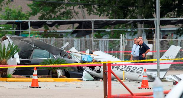 Authorities investigate the scene where a small plane crashed into a car in a parking lot near a Houston airport on Thursday, June 9, 2016