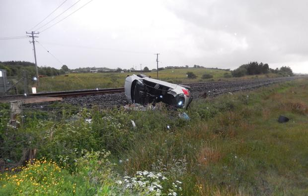 A car overturned on railway tracks