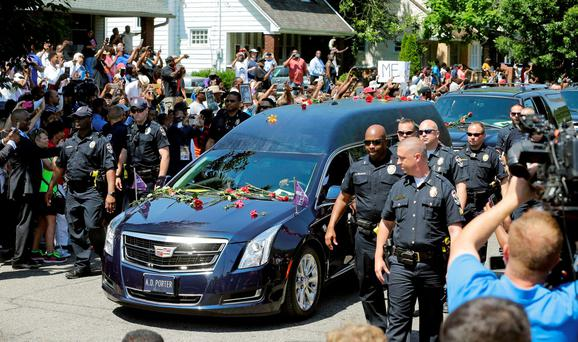 The hearse carrying the body of Muhammad Ali travels down the street of his boyhood home during his funeral procession, in Louisville. (AP Photo/Mark Humphrey)