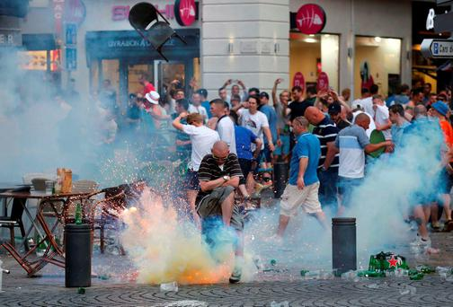 A teargas grenade explodes near an England fan in Marseille. Photo: Reuters