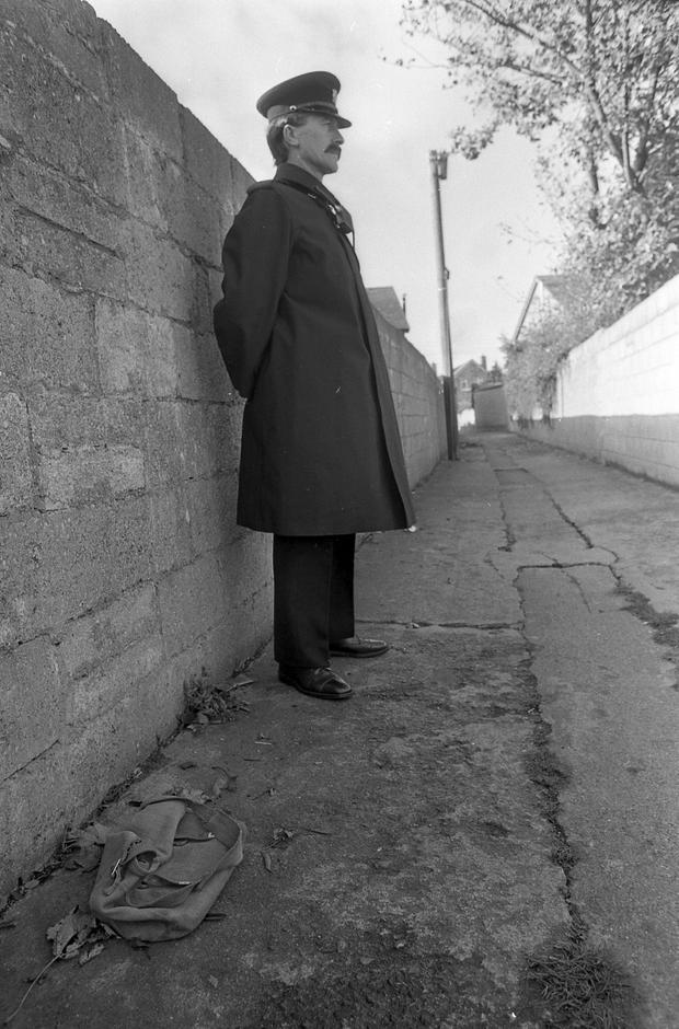 A garda on duty at the laneway on Ballyroan Road, Rathfarnham, from where Philip went missing on October 23, 1986. His schoolbag is on the ground.