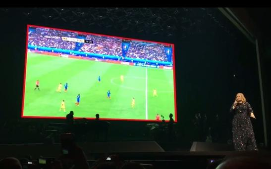 Adele plays the France v Romania game on the big screen during her concert in Paris. Photo: Twitter / Benjamin Raibier