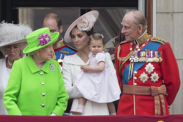 (L-R) Britain's Queen Elizabeth II, Britain's Catherine, Duchess of Cambridge holding her daughter Princess Charlotte and Prince Philip, Duke of Edinburgh watch a fly-past of aircrafts by the Royal Air Force, in London on June 11, 2016. Trooping The Colour and the fly-past are part of a weekend of events to celebrate the Queen's 90th birthday. / AFP / JUSTIN TALLIS