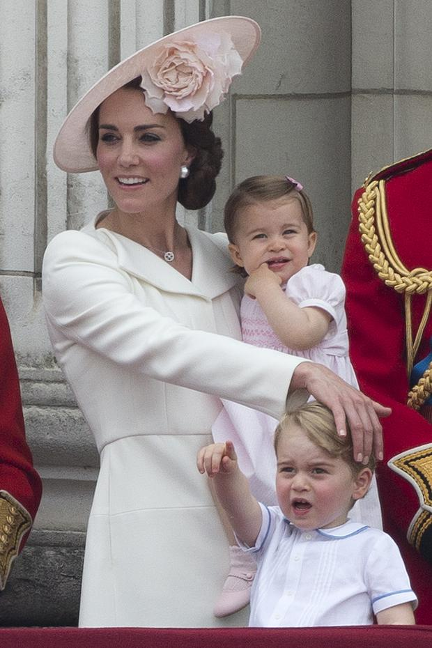 Britain's Catherine, Duchess of Cambridge holds her daughter Princess Charlotte and strokes her son, Prince George's head as they stand on the balcony of Buckingham Palace to watch a fly-past of aircrafts by the Royal Air Force