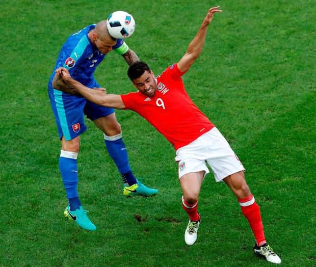 Wales's Hal Robson Kanu challenges for the ball with Slovakia's Martin Skrtel. Photo: Hassan Ammar/AP Photo