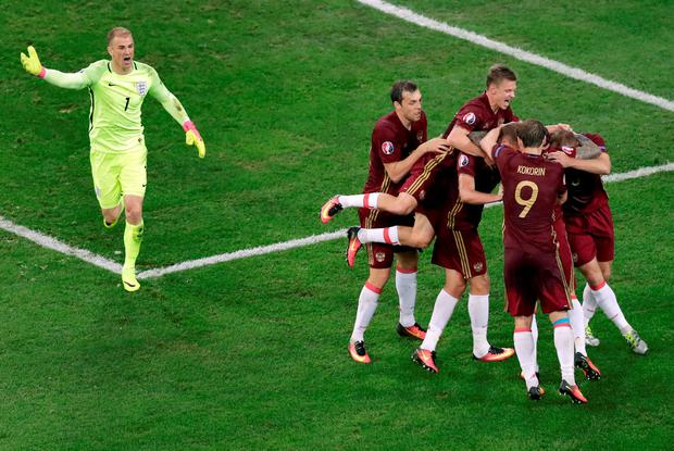 England goalkeeper Joe Hart, left, reacts as Russia's players celebrate their side's goal Photo/Ariel Schalit)