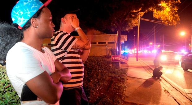 Jermaine Towns, left, and Brandon Shuford wait down the street from a multiple shooting at a nightclub in Orlando, Fla., Sunday, June 12, 2016. Towns said his brother was in the club at the time. (AP Photo/Phelan M. Ebenhack)