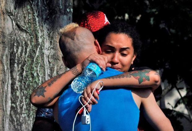 Friends and family members embrace outside the Orlando Police Headquarters during the investigation of a shooting at the Pulse nightclub, where people were killed by a gunman, in Orlando, Florida, U.S June 12, 2016