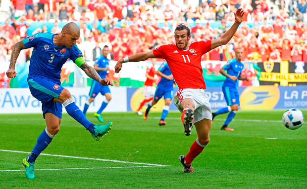 Slovakia's defender Martin Skrtel kicks the ball past Wales' forward Gareth Bale during the match between Wales and Slovakia. Photo: Joe Klamar/Getty Images
