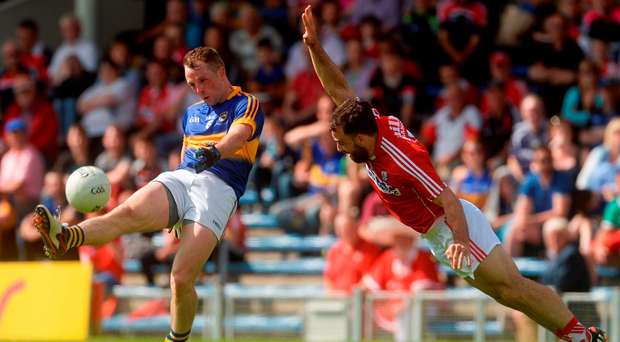 Peter Acheson of Tipperary scores a point under pressure from Colm O'Driscoll. Photo by Piaras Ó Mídheach/Sportsfile