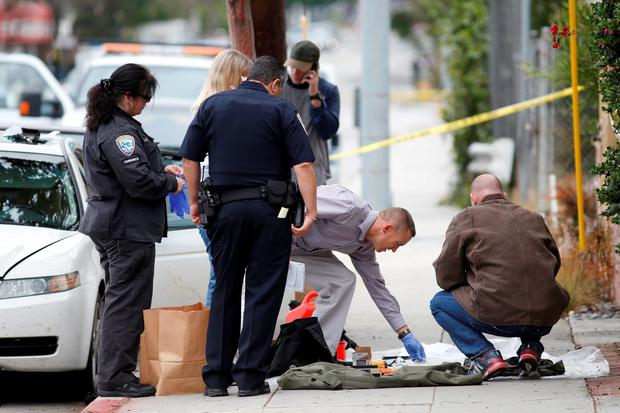 Investigators work a crime scene around a white Acura vehicle after the arrest of a man found with assault weapons and possible explosives, who told authorities he was in town for the city's gay pride parade in Santa Monica, California, U.S. Photo: Reuters