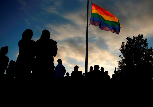 Mourners gather under an LGBT pride flag flying at half-mast for a candlelight vigil in remembrance for mass shooting victims in Orlando, from San Diego, California, U.S. June 12, 2016. REUTERS/Mike Blake