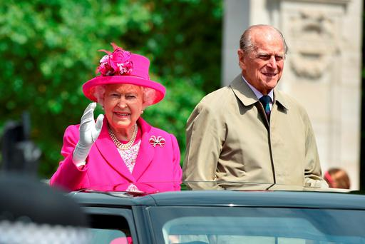 Queen Elizabeth II and Prince Philip, Duke of Edinburgh wave to guests attending