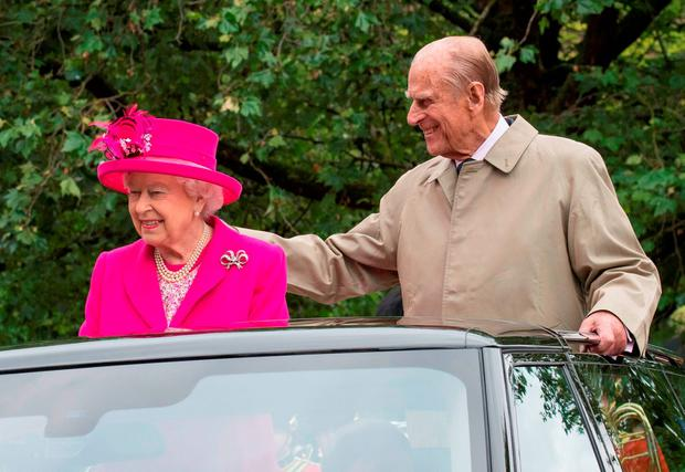 Britain's Queen Elizabeth II and Britain's Prince Philip, Duke of Edinburgh are driven along the Mall during the Patron's Lunch, a special street party outside Buckingham Palace in London on June 12, 2016, as part of the three day celebrations for Queen Elizabeth II's official 90th birthday
