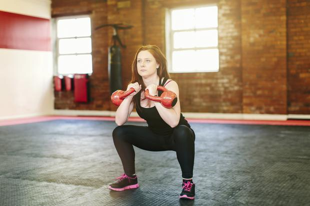 Woman squatting lifting kettlebells
