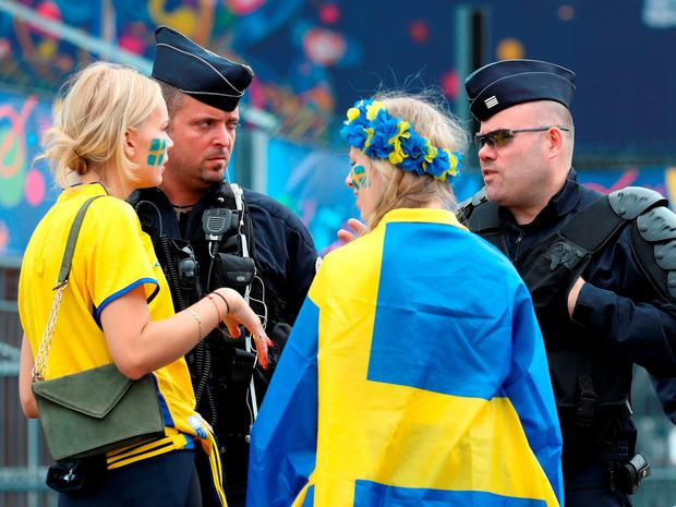 Sweden fans speak to gendarmes outside the stadium ahead of the game with Ireland