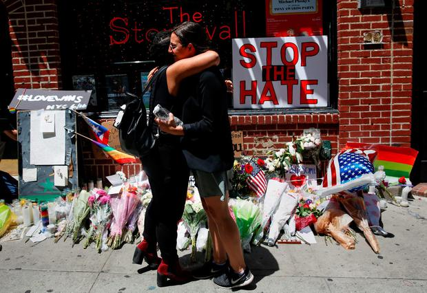 Matti Mejia (left) and Shaina Roberts embrace after laying flowers at a memorial in New York for the Orlando victims. REUTERS/Shannon Stapleton