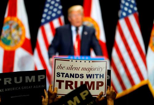 Supporters hold up signs while listening to Republican U.S. presidential candidate Donald Trump during a campaign rally in Tampa, Florida. REUTERS/Scott Audette