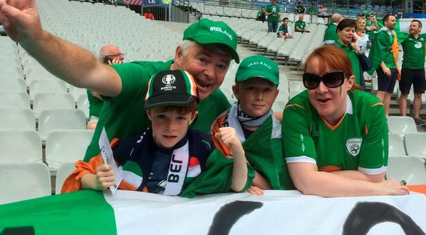 Peter O'Connell with his sons Stephen (9) and Eoin (7) and their pal Carole Murphy pose with the flag shortly before the game