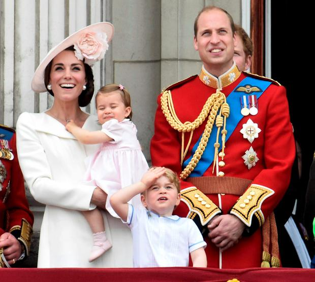 Catherine, Duchess of Cambridge holding Princess Charlotte, Prince George and Prince William, watch a flypast as they stand on the balcony of Buckingham Palace after the annual Trooping the Colour ceremony on Horseguards Parade
