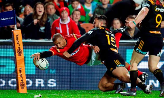 Eli Walker (L) of Wales is tackled short of the line by Waikato Chiefs player James Lowe (C) during the rugby union match between the Super Rugby team Waikato Chiefs and Wales at FMG Stadium in Hamilton