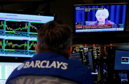 Traders work on the floor of the New York Stock Exchange (NYSE) as a television screen displays coverage of US Federal Reserve Chairmman Janet Yellen. Photo: Reuters