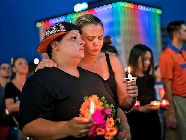 Nicole Edwards and her wife Kellie Edwards observe a moment of silence during a vigil outside the Dr. Phillips Center for the Performing Arts for the mass shooting victims at the Pulse nightclub June 13, 2016 in Orlando, Florida. (Getty)