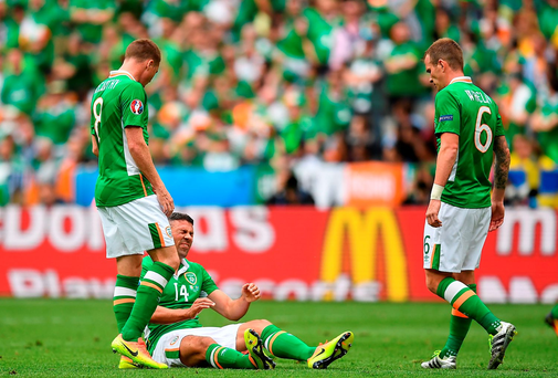 Jon Walters, centre, of Republic of Ireland reacts after a tackle while team-mates James McCarthy, left, and Glenn Whelan watch on