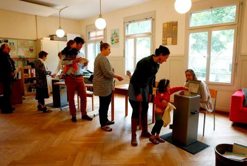 People vote in a recent referendum on whether to give every adult citizen a basic guaranteed monthly income of 2,500 Swiss francs, in a school in Bern, Switzerland. Photo: Ruben Sprich/Reuters