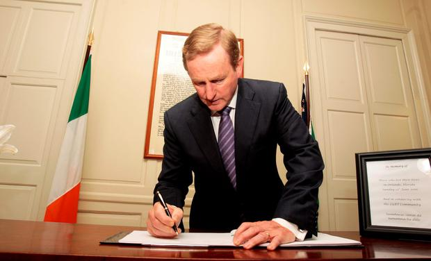 Taoiseach Enda Kenny signs the book of condolence for the victims of the massacre at the Mansion House yesterday .Pic Tom Burke
