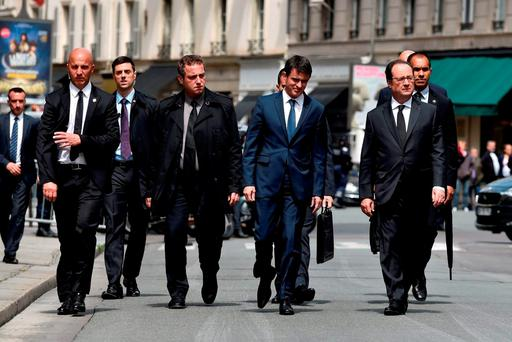 French Prime Minister Manuel Valls (L), and French President Francois Hollande (R), walk back to the Elysee palace in Paris after a ceremony at the Ministry of Interior to pay a tribute to a French policeman and his partner, who were killed on June 13 by a man claiming allegiance to the Islamic State group. GETTY