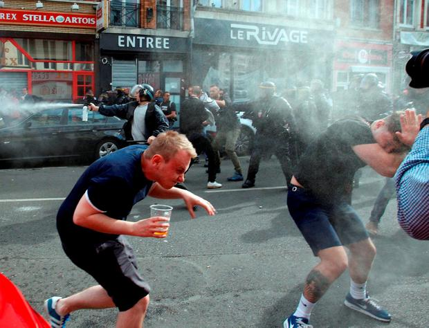 Riot police use tear gas on English fans at Lille train station. AP