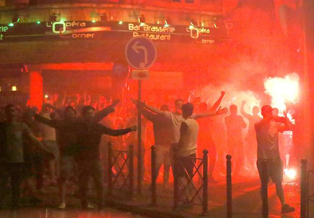 England fans lit by a burning flare in Lille city centre, France, as fresh clashes have taken place between England fans and Russian hooligans at Euro 2016. Niall Carson/PA Wire