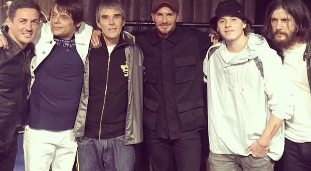 David Becnkham and son Brooklyn meet Stone Roses backstage at Manchester gig.