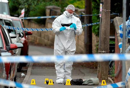 police forensic officer picks up a shoe from the crime scene on the pavement outside the library in Birstall where Jo Cox was shot. Getty Images