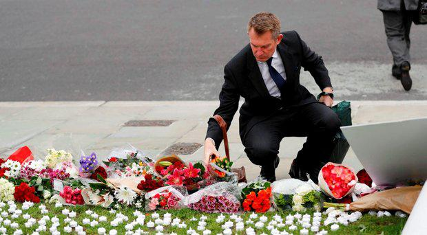 A man leaves a floral tribute for murdered Labour Member of Parliament Jo Cox in Parliament Square, London, Britain June 17, 2016