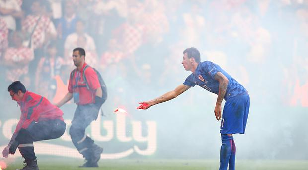 SAINT-ETIENNE, FRANCE - JUNE 17: Mario Mandzukic of Croatia reacts as flares are thrown onto the picth during the UEFA EURO 2016 Group D match between Czech Republic and Croatia at Stade Geoffroy-Guichard on June 17, 2016 in Saint-Etienne, France. (Photo by Clive Brunskill/Getty Images)