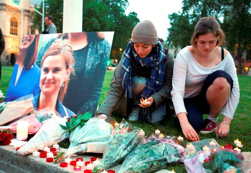 Floral tributes and candles are placed by a picture of slain British Labour MP Jo Cox at a vigil in Parliament Square, London. Photo: Daniel Leal-Olivas