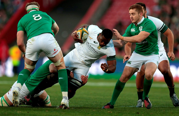 South African Siya Kolisi (C) dives through Ireland defense during the second Rugby Test match between South Africa and Ireland at Ellis Park on June 18, 2016 in Johannesburg. / AFP PHOTO / GIANLUIGI GUERCIAGIANLUIGI GUERCIA/AFP/Getty Images