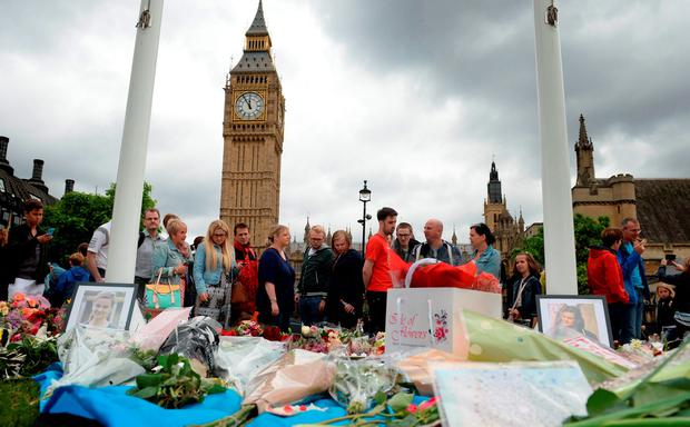 Members of the public look at flowers and tributes to the murdered MP outside the Houses of Parliament yesterday. Photo: PA