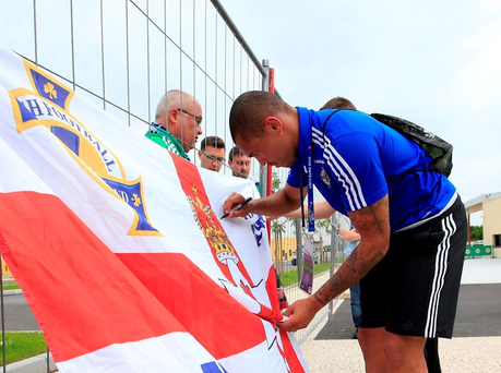 Northern Ireland's Josh Magennis signs a fans flag before attending a press conference at weekend Saturday. Photo: Jonathan Brady/PA