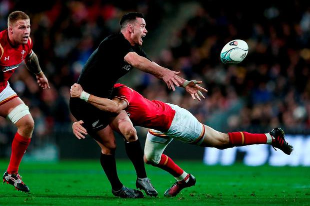 Ryan Crotty of New Zealand offloads in the tackle from Liam Williams of Wales. Photo by Anthony Au-Yeung/Getty Images
