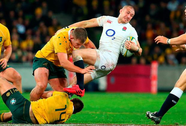Mike Brown of England is tackled by Toby Smith of the Wallabies. Photo by Scott Barbour/Getty Images