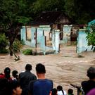 People stand in front of a flooded area in Kampung Sewuresidential area in Solo, Central Java province, Indonesia, June 19, 2016. Antara Foto/Maulana Surya/via REUTERS